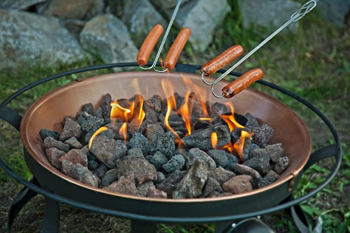 Hot dogs roasting over a portable fire pit
