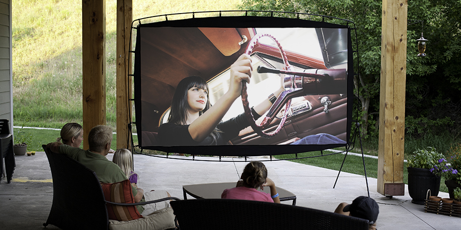 Family watching a movie on an outdoor movie screen